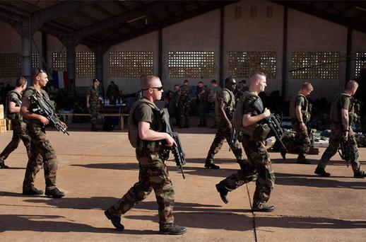 French soldiers walk past a hangar they are staying at the Malian army air base in Bamako
