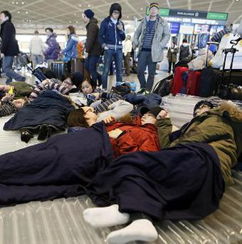 Travellers rest on the floor at a departure lobby at Narita airport near Tokyo as they stayed overnight due to heavy snow (AP/Kyodo News)