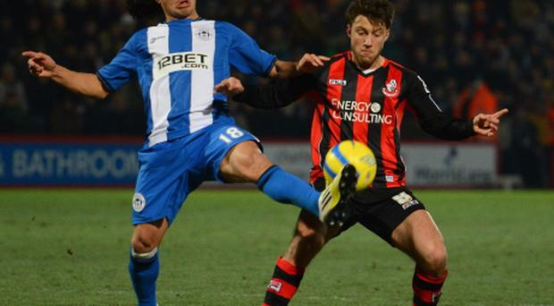 BOURNEMOUTH, ENGLAND - JANUARY 15: Roger Espinoza of Wigan is challenged by Harry Arter of Bournemouth during the FA Cup Third Round Replay between AFC Bournemouth and Wigan Athletic at Goldsands Stadium on January 15, 2013 in Bournemouth, England. (Photo by Mike Hewitt/Getty Images)