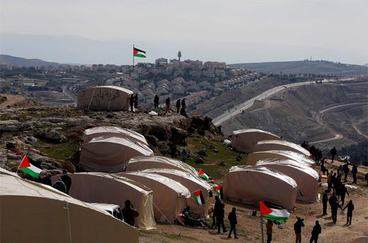 Palestinians, together with Israeli and foreign activists, stand near newly-erected tents in an area known as E1, near Jerusalem. Photo: Reuters