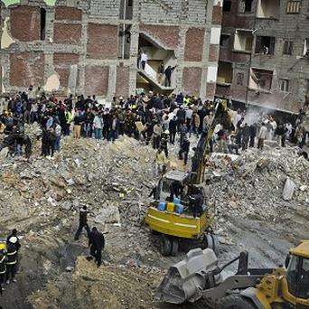 Egyptians stand in the rubble after the buidling collapse (AP)