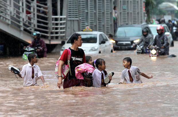 Schoolchildren cross a flooded area at the business district in Jakarta . Photo: Reuters