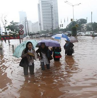 Workers wade through a flooded street in Jakarta (AP)