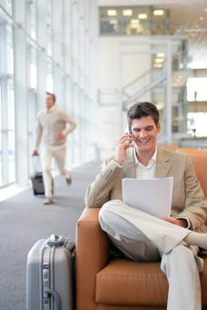 Businessman using a cell phone and laptop, businessman with luggage in background