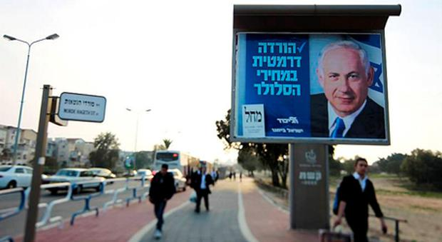 People walk past a campaign poster depicting Israel's Prime Minister Benjamin Netanyahu in the southern city of Ashdod