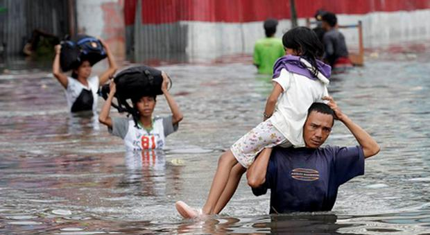 A man carrying his daughter on his shoulders walks through flood waters followed by his family in west Jakarta