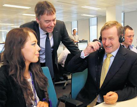 Taoiseach Enda Kenny takes a call from a customer while service adviser Sarah Callanan and BSkyB chief executive Jeremy Darroch look on