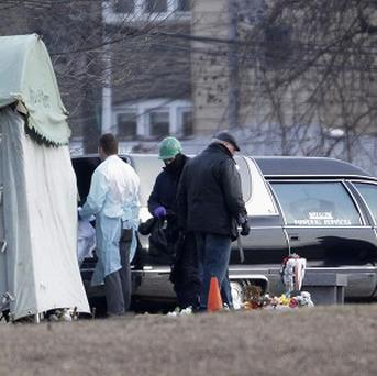 Workers at Rosehill Cemetery in Chicago place the body of Urooj Khan into a hearse after it was exhumed (AP/M Spencer Green)