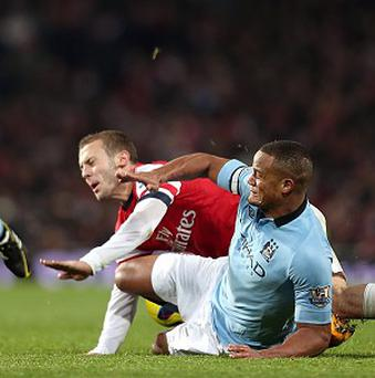 Vincent Kompany, right, was sent off for a lunge on Jack Wilshere