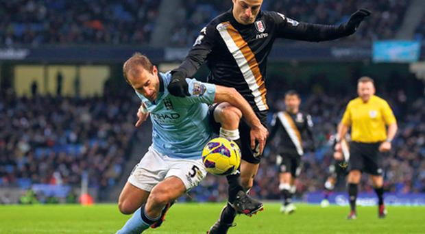 Pablo Zabaleta of Manchester City challenges Fulham's Dimitar Berbatov during their Premier League encounter at the Etihad Stadium yesterday