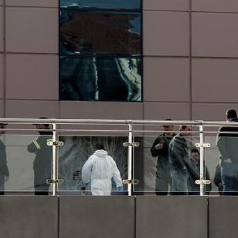 Greek security officers stand outside a mall following a blast in Athens (AP)