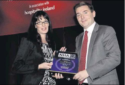 Helen Woods Heaton receiving the Overall Award for Best Value Hotel at the National Hospitality Awards from Mark Kelly, publisher at Madison Publications, in the Four Seasons Hotel in Dublin recently.