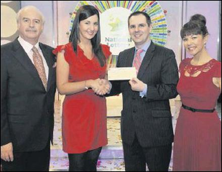 Tara Callaghan, from Red Barns Road, Dundalk, with Marty Whelan, game show host, Nigel Scully, Head of Sales, National Lottery, and Geri Maye, game show host.