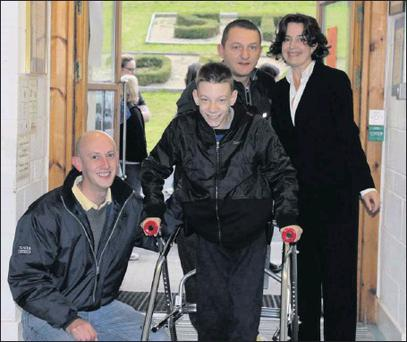 Michael Tiron walking into St. Cronin's School for the first time watched by Karl Ó'Broin (Michael's Teacher), Marcel Tiron (Michael's Father) and Maeve Tierney (School Principal).