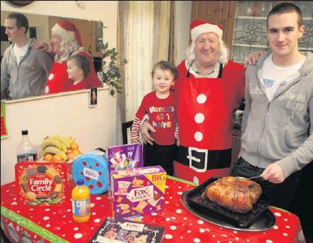 Bill Burke still going strong after 21 years cooking the Knights of Columbanus Christmas dinner but with a little help from his grandsons Liam Burke and Eden Doyle.
