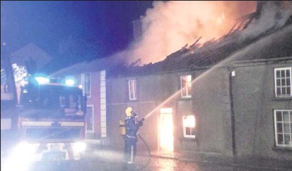 Firemen tackle the blaze that claimed the life of Timothy Arnold on Sunday evening on Main St, Rathcormac.