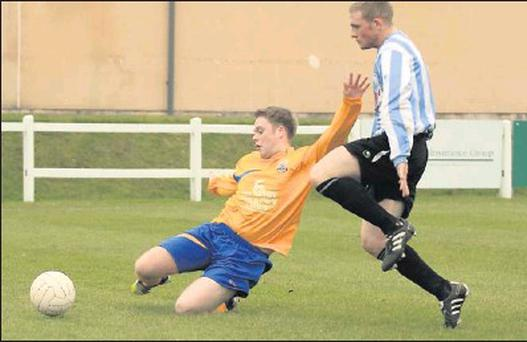 Fermoy's Dave Clancy makes a sliding clearance before Glen Celtic's Paul Kenneally can close him down. Photo: Eric Barry