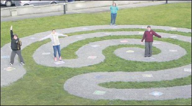 Amy Begley, Cliona McMahon, Gemma and Charlotte Mahony standing beside their painted slabs in the 'Life Path' Labyrinth which is located in the Gilbert Centre in Mallow.