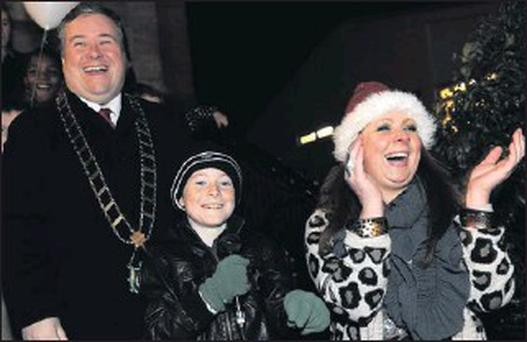 Mayor Paul Bell and MC Kelly Kierans cheer as Sean McCarron flicks the switch to turn on the Christmas lights on West Street in Drogheda on Friday evening.