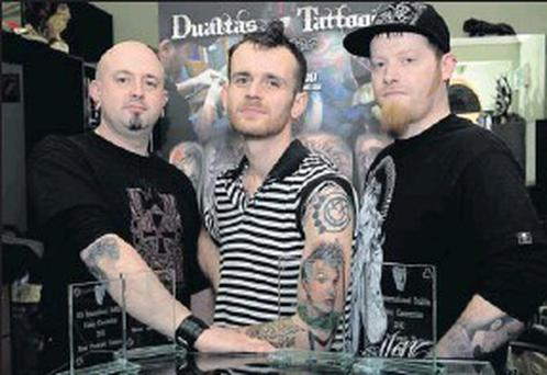 Dave Murray, John Boy Sullivan (displaying the award-winning tattoo of Blink 182's Mark Hoppus) and Dualta Kellegher with the two awards Dark Valley Tattoo won.