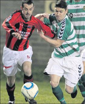 Danny Coyle (Drogheda Town) tries to escape the clutches of Dublin Bus's Patrick Mohan during Friday's Leinster Senior League clash at Marian Park. -Match report on Page 87