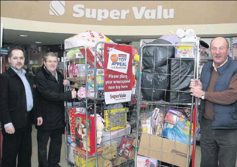 Daniel Kovac (Manager of SuperValu at Mill Park Road) with St Vincent de Paul representatives Rory McCauley and Dessie Sheehan, and some of the toys donated this year.
