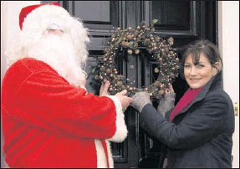 Santa giving Kelly Browne of the Tae Lane Boutique a hand with the decorations in Listowel in the run-up to the Christmas season. Credit: Photo by John Reidy