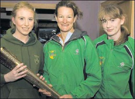 Sonia O'Sullivan pictured with Cordal sisters, Amy (left) and Katie Reidy when she visited An Riocht Athletic Club on Sunday November 18 last. Sonia and Amy are holding a replica of the Olympic torch holder with which each person who carried the... Credit: Photo by John Reidy