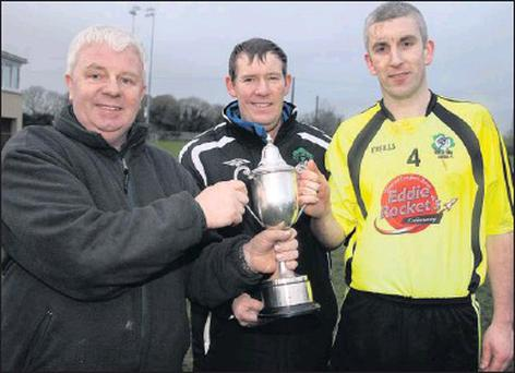 KDL officers, John O'Regan (left) and Seán O'Keeffe presenting Killarney Celtic captain, Brian Spillane with the Munster Junior / Kerry Area cup after his side's win over Listowel Celtic Photo: John Reidy