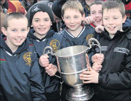 A day to remember: Young Duagh fans of all ages gather around the North Kerry SFC Cup after their club defeated Beale in the replayed 2012 final in Listowel on Sunday to win the title for Duagh for the first time since 1962. Credit: Photo by John Reidy