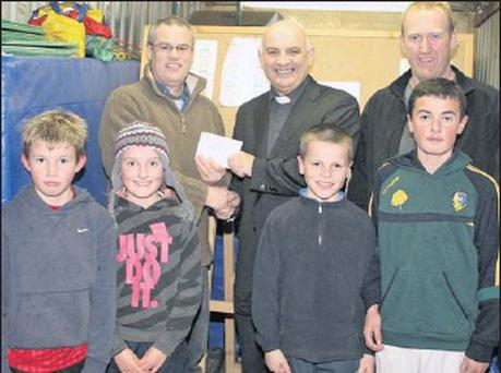 Front: young athletes Darragh and Aine Mc Donald, Jack Ryan and Jack Elliot with Denis Power, Fr Dan Cavanagh and Tom McDonald at the cheque presentation in Rosbercon.