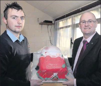 Good Counsel College student Lar Whelan with his Christmas cake he made to raffle in the college in aid of Pieta House, seen here with Fr. John Hennebry, principal.