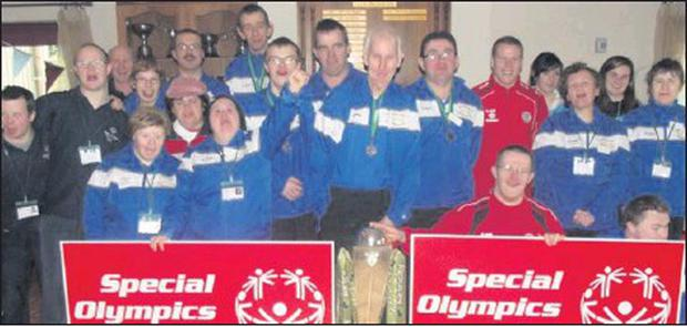 Local Special Olympics athletes and volunteers with the FAI League Trophy at the regional badminton qualifiers in Sligo Tennis Club.