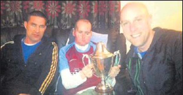 Kerry McKeon, winner of the Eastern Harps sports prediction competition, pictured with Curry stars, Sean Davey and Kenneth Morley and the Owen B Hunt Cup.