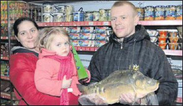 Justine, Oliwia and Slawek Gendola pictured with a carp, which is part of the traditional Polish Christmas Eve dinner.