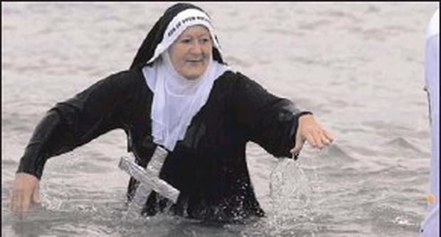 Mary Burke takes a chilly New Year's dip while doing her 'sister act' for charity.