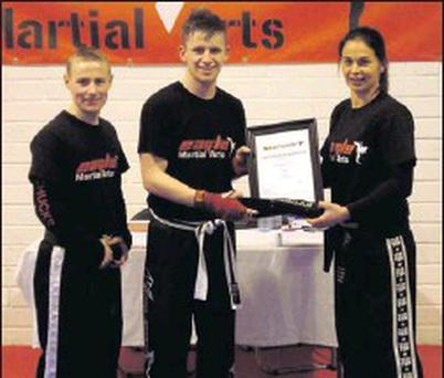 Barry Coughlan is presentaed with his Black Belt by Chief Instructor Julie McHale, 4th Degree Black Belt, watched by Sensei James Stuart.