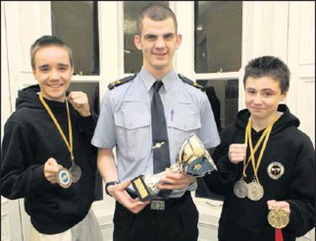 Tae Kwan Do success stories Killian Hannon and Alex Connolly from East Coast Tae Kwan Do at Bray Garda Station with Olympian Adam Nolan, displaying their medals and honours.