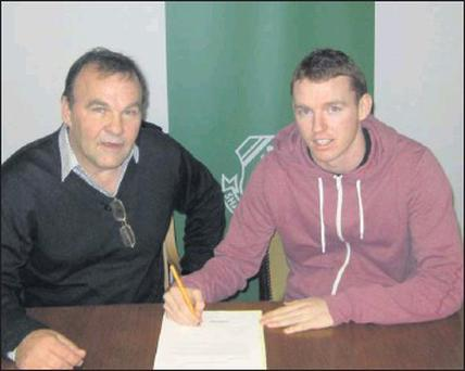 Danny Ledwith seen signing the contract with Shamrock Rovers alongside Rovers' secretary Noel Byrne.