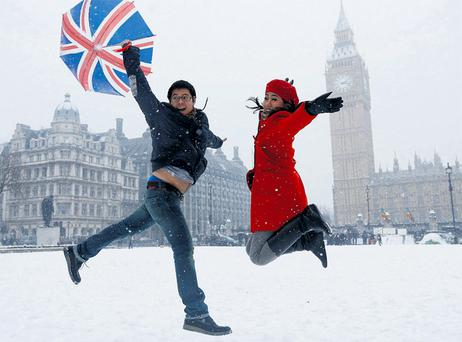 Some like it not so hot: Pandu and Dian, tourists from Indonesia, jump for a souvenir photograph in front of the Houses of Parliament in London