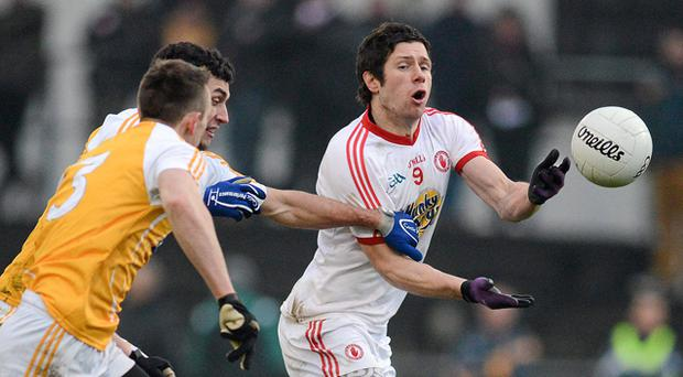 Sean Cavanagh, Tyrone, in action against Paul Docherty and Colm Fleming, Antrim. Photo: Sportsfile