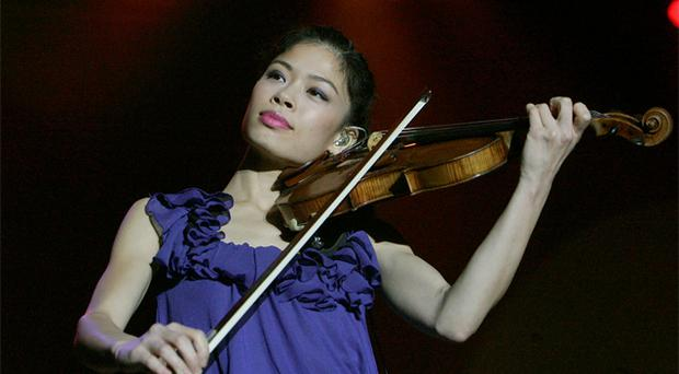 Violinist Vanessa Mae is seen performing on stage during a concert in Prague. She has put music on hold for a year and is rehearsing for a new role -- skiing for Thailand at the Winter Olympics. Photo: Reuters