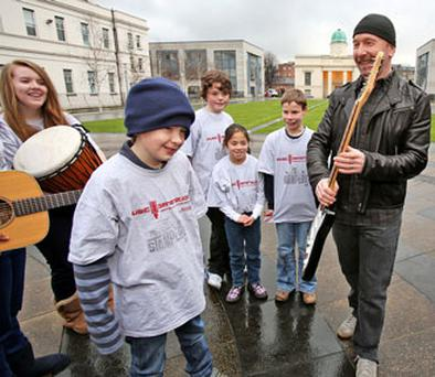 The Edge admires 10 year old Chris Farrell's beanie hat at the Department of Education this morning at the announcement of a funding initiative by the Department of Education, the U2 and Ireland Funds, supported by National Music Education Programme for Music Generation to develop music education in Ireland.