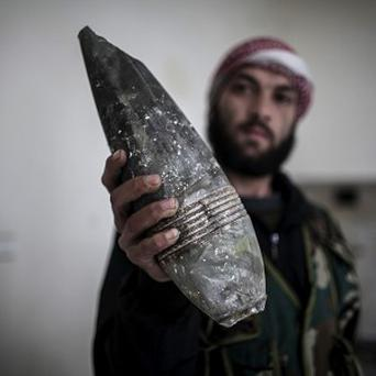 A Free Syrian Army fighter displays used ordinance from government forces in Aleppo, Syria (AP)