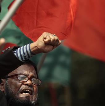 A Bangladeshi activist shouts slogans as he celebrates outside the International Crimes Tribunal court building in Dhaka (AP)