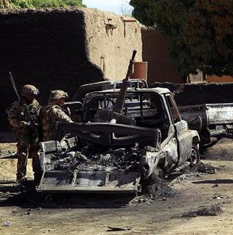French troops inspect the charred remains of military vehicles used by radical Islamists on the outskirt of Diabaly, Mali (AP)