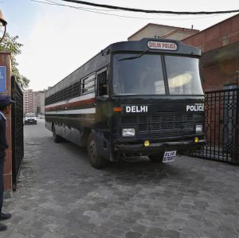A Delhi police van, believed to be carrying the five men accused of raping and murdering a woman on a bus, comes out of a district court in New Delhi (AP)