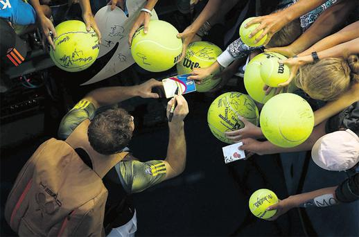 Andy Murray keeps the autograph hunters happy after brushing past the challenge of Gilles Simon in Melbourne