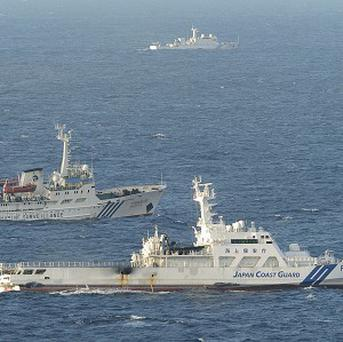 The Japan Coast Guard vessel Yonakuni and the Chinese surveillance vessel Haijian 137 sailing around 20 miles north of Uotsuri Island (AP)