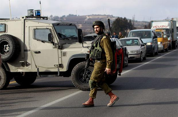 An Israeli soldier walks in front of a military vehicle blocking traffic on a road near the scene of a shooting in al-Arroub refugee camp near the West Bank city of Hebron. Photo: Reuters